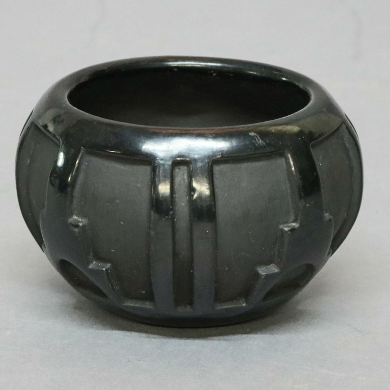 An American Indian pottery vase by Robert Naranjo, Santa Clara features bulbous vessel with sculpted repeating geometric design having matte and gloss glaze, en verso Artist-signed as photographed, 20th century  ***DELIVERY NOTICE – Due to COVID-19