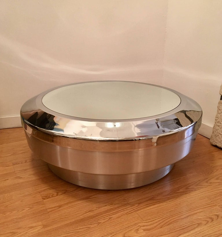 A sleek modern American 1960s coffee table designed by John Neville. The table is composed of a brushed silver metal base with a polished chrome rim top and a mirror glass.