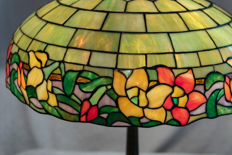 This colorful lamp made by Wilkinson as a graceful floral border of orange, green, yellow and purple tiles. The upper geometric brickwork design section is comprised of yellowish-green tiles. The handsome base is factory patinated in a rich dark
