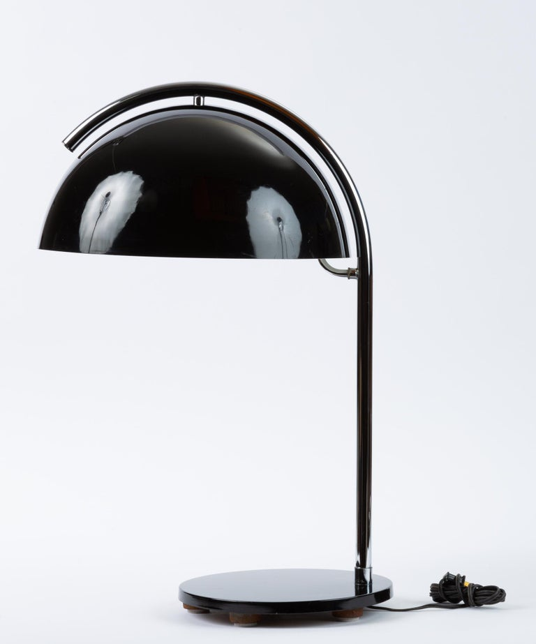 A tall table lamp with an arcing steel arm and a generous mushroom lampshade in black-enameled metal. A round base in matching black anchors the lamp, concealing a stabilizing weighted iron foot. A curved steel branch reaches from the arm beneath