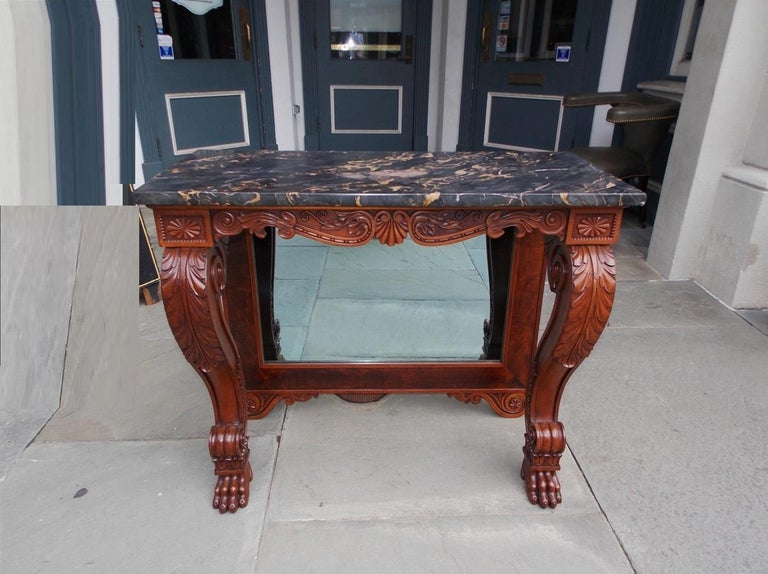 American mahogany marble-top console / pier table with acanthus scrolled legs, flanking corner beaded medallions, decorative scrolled acanthus skirt with centered shell motif, original mirror with wood backing and resting on carved lions paw feet,
