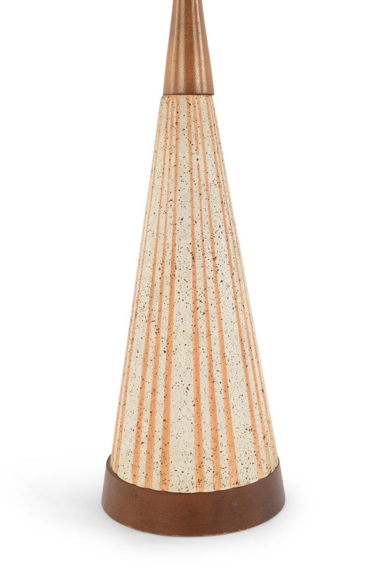 American midcentury (1960s) beige cone shaped ceramic table lamp with an orange fluted design resting on a round wood base with a similar tapered top.