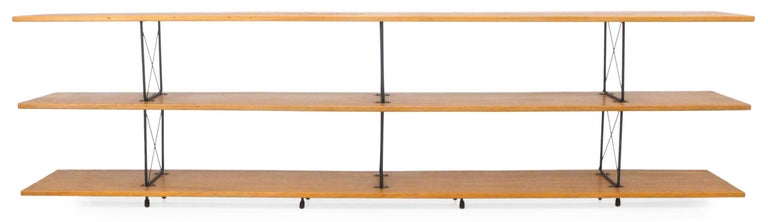 A wonderful, American midcentury shelving unit in wood and iron. Assembled from a kit of D.I.Y. X-brace hardware and beautiful, mitered-edge, solid wood planks, a clearly Eames/McCobb inspired design quite well assembled. Retains original