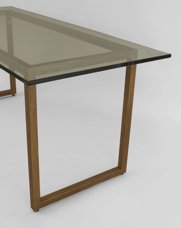 American Mid-Century Modern style gold painted metal base dining table supporting a large rectangular glass top.