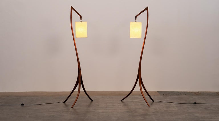 Matching floor lamps, walnut, linen, USA, 1960.  Glamorous and simply sculptural pair of floor lamps from 1960s. The beautifully curved feet and the pole are made of walnut. The pair not only exhibits an elegance, but also artful craftsmanship