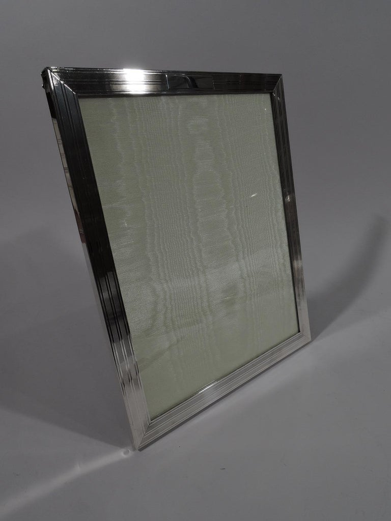 American modern sterling silver picture frame, circa 1940. Rectangular window in flat surround with wraparound engine-turned lines and rectangular cartouche (vacant). With glass, silk lining, and wood laminate back and hinged support. For portrait