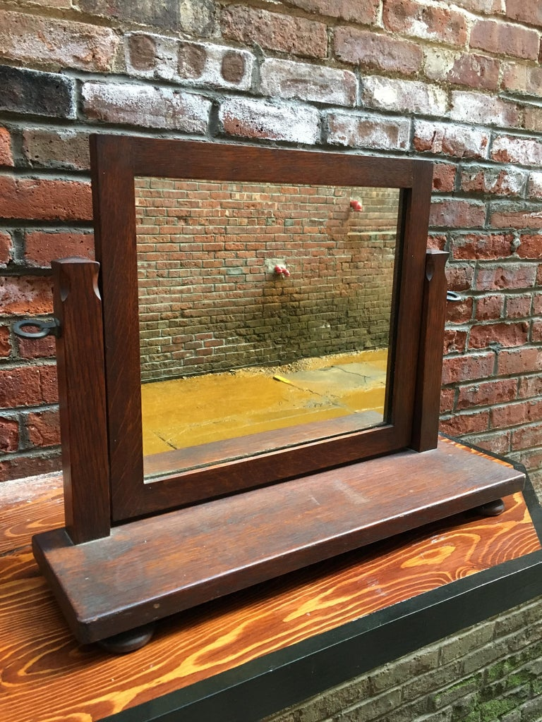 Constructed from solid American white quarter sawn oak. Adjustable mirror, carved posts resting on four bun feet. Old dark finish, circa early 20th century. Great for an overmantel, tabletop or dresser.  Measures: 6.75