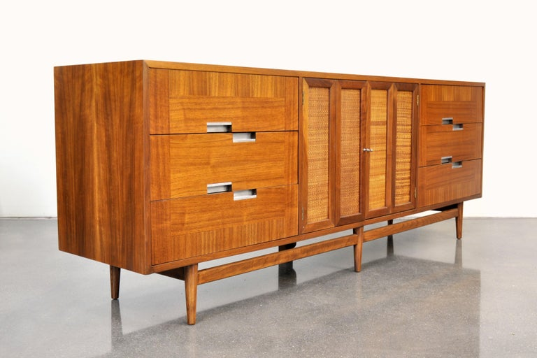 A gorgeous 7 foot long Mid-Century Modern walnut credenza from the desirable Accord line manufactured by American of Martinsville in the 1960s. The dresser features three drawers with aluminum pulls on the left and right sides centering a pair of