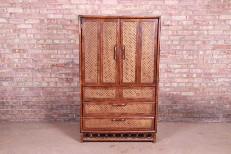 A gorgeous Mid-Century Modern Hollywood Regency highboy dresser chest.  By American of Martinsville,  USA, circa 1960s  Walnut, with woven rattan panels, bamboo base, and original brass hardware.  Measures: 38
