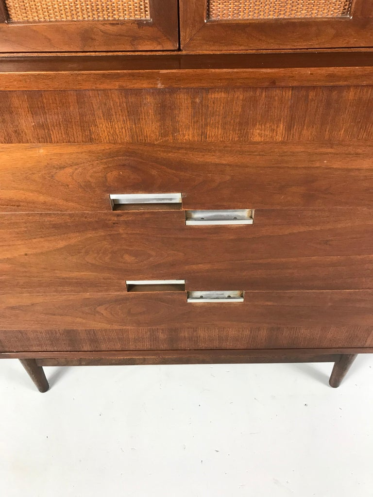 """This stylized dresser features contrasting walnut veneer, two doors with four rattan panels, and this lines signature inset nickel """"x"""" on each corner of the top. Rich walnut grain graces all surfaces. With an angular profile, this vintage piece has"""