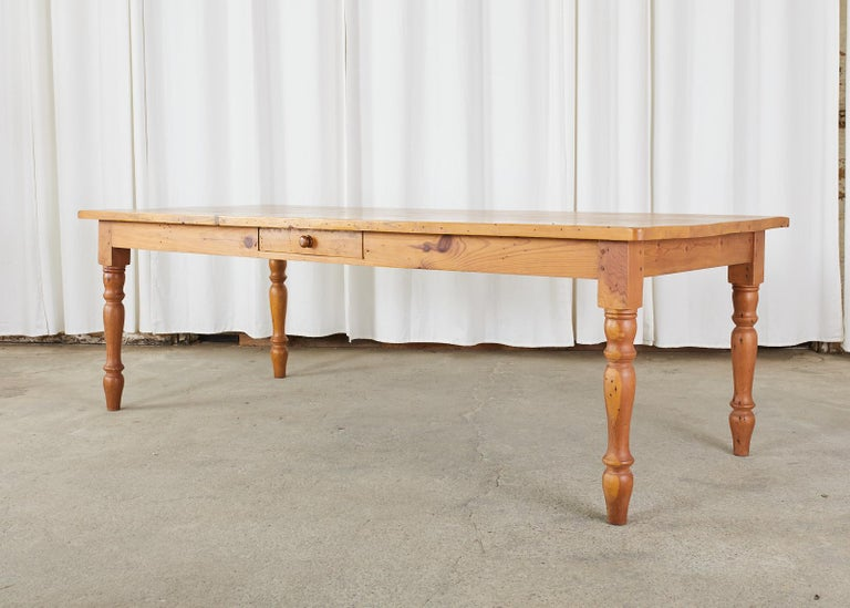Rustic American pine dining table made in the country farmhouse style. The large top is made from 1.25 inch thick planks of pine. Supported by thick, turned legs on each corner. Ample legroom measuring 25 inches from the floor to the apron. The