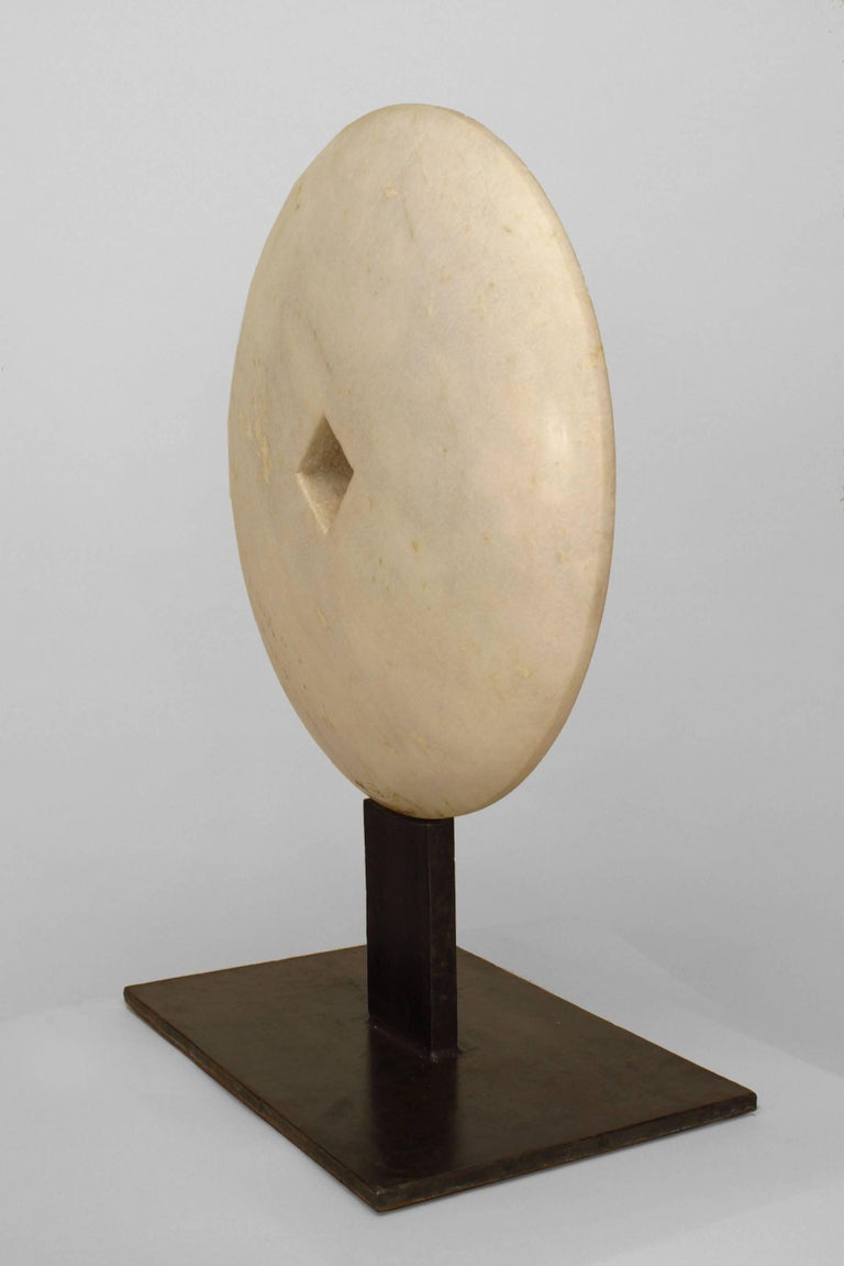 American Post-War Design style abstract sculpture of light grey marble disc with a cut-out square center mounted on a rectangular iron base. (modern)
