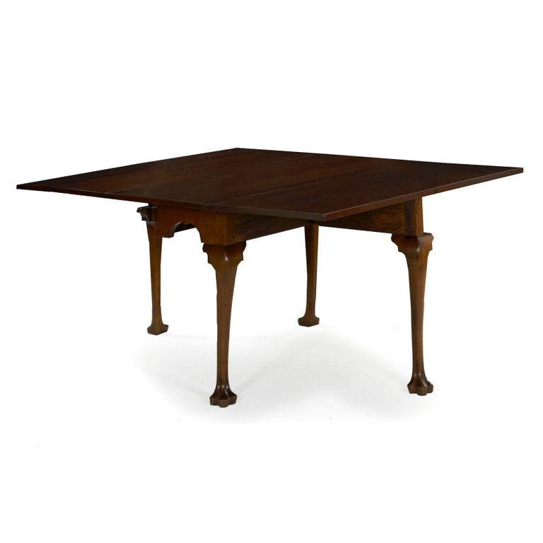 A fine Queen Anne walnut drop-leaf dining table from the third quarter of the 18th century, it is characterized by an arched skirt with a tiny drop at the centre over cabriole legs terminating in carved trifid feet. The leaves are raised over
