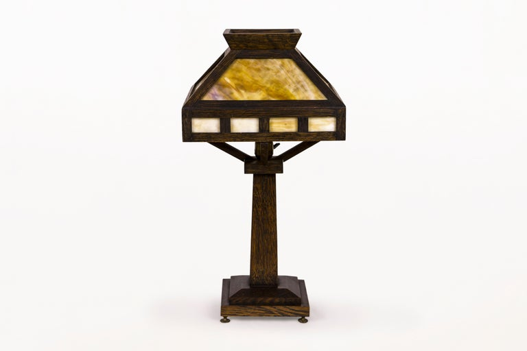 American Rustic Mission oak table lamp Classic Arts & Crafts oak table lamp. The lamp has a four sided shade with caramel slag glass insert and a footed base. All original finish with a rich patina. Lamp is in very good original condition with