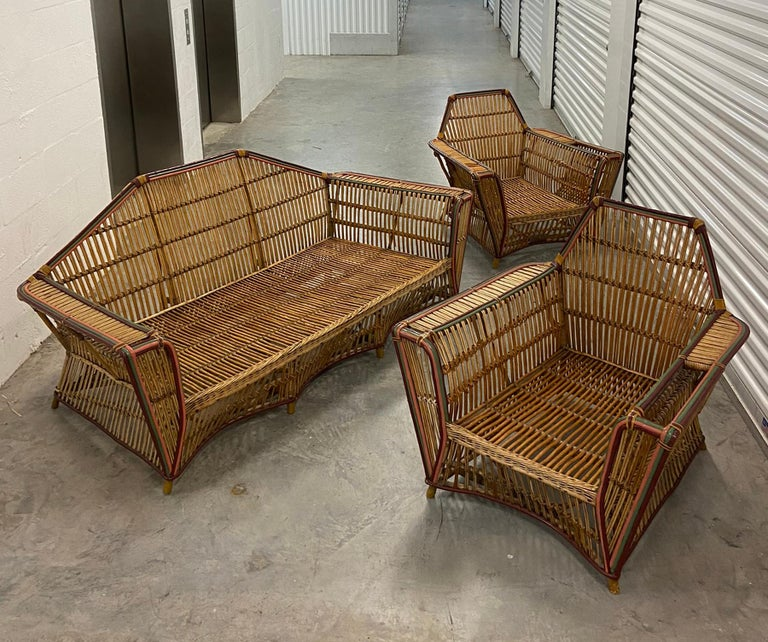 1920s three-piece American split reed stick wicker living room suite. Sofa and two club lounge chairs. Retains original finish with some touch up and minor repairs. Has passable cushions but you probably want to have them re-worked and recovered
