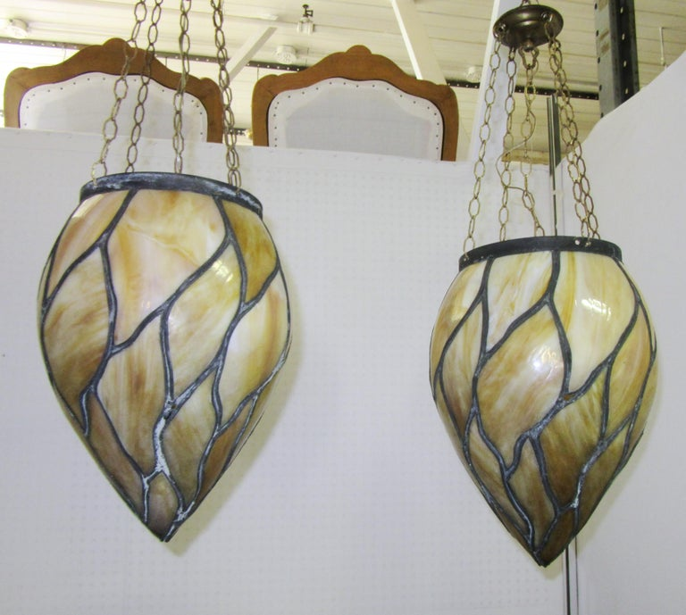 American late Victorian pair of caramel slag stained glass pendants. The pair was made in the United States in the 1910s. The chain can be shortened if needed.