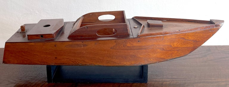 American vintage model of a Speedboat 'Ricky-O' Well crafted in mahogany with numerous details, The stern is inscribed 'Ricky-O' with a blue bottom. Complete with an ebonized display stand. Great color and patina.  The boat stand measures 15.75