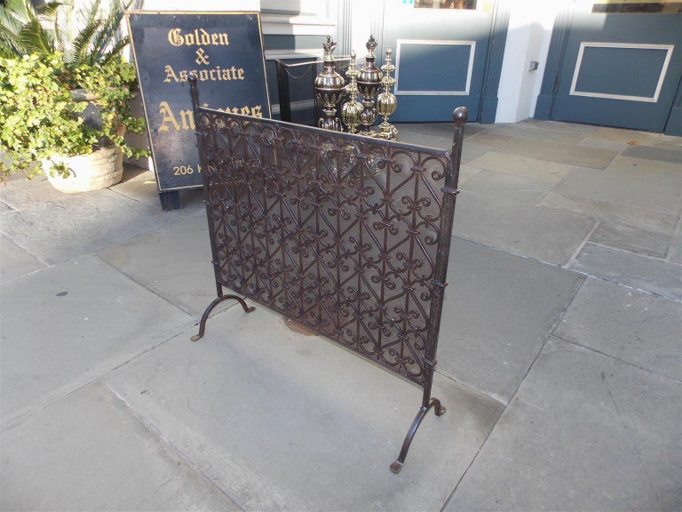 American wrought iron free standing fire screen with flanking ball finials, decorative scrolled centered panel with interior lined mesh, tapered supporting columns, and terminating on scrolled legs with stylized penny feet, Early 19th Century.