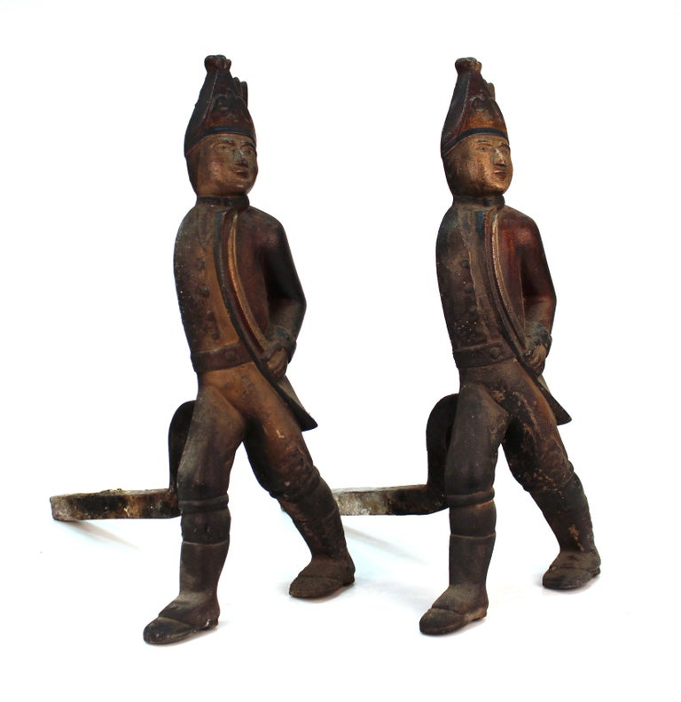 Americana Hessian soldier andiron pair in painted cast iron. Wear includes heavy patina to metal appropriate to age, use and materials. The pair is in good condition.