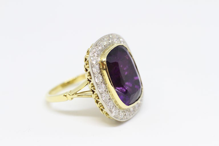 Amethyst and diamond cocktail cluster ring set with a cushion shape amethyst in an open back rub-over setting with an approximate weight of 13.00 carats, surrounded by twenty four round brilliant cut diamonds of fine quality in grain settings with a
