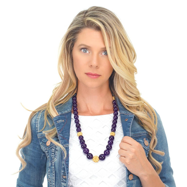 Circa 1960s, 18k, Switzerland.  This vision in lush purple and gold features vibrant amethyst beads interspersed with textured gold floral elements. Finely made, this vibrant necklace is perfect for everyday and converts into a shorter necklace and