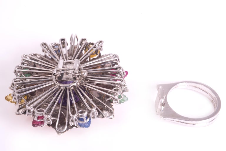 Flower ring in white and rose gold 18 kt engraved, it disassembles and becomes a pendant with brilliants ct 0,48 and leaves of sapphires ct 0,30, rubies ct 0,30, emeralds ct 0,30, yellow sapphires ct 0,30 and central oval amethyst ct 14