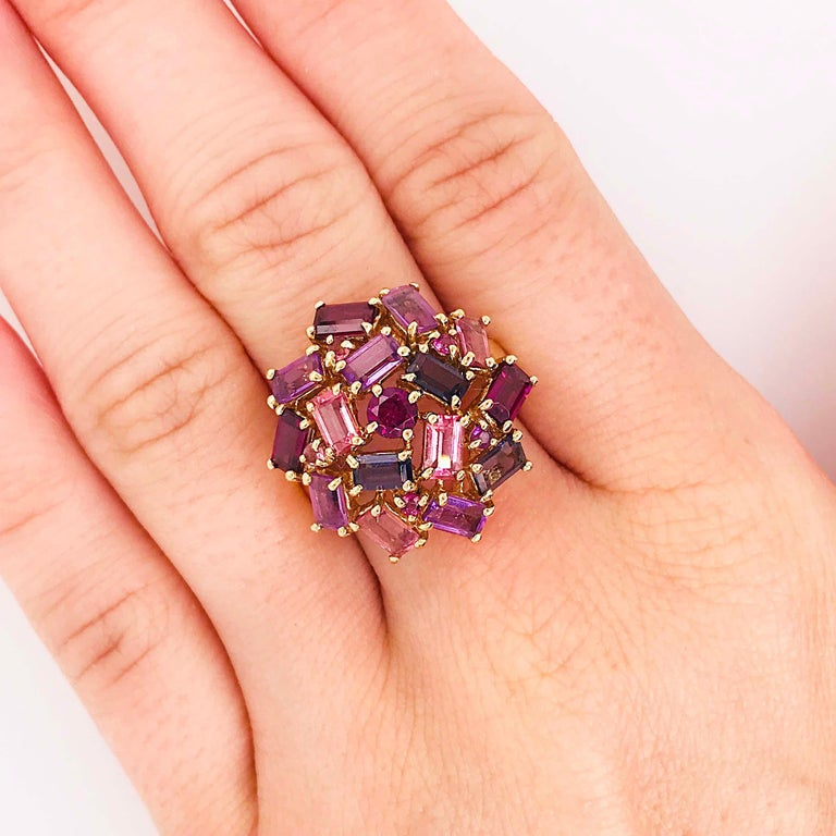 The gorgeous purple gemstone cluster ring is a one of a kind item! Made with all natural and genuine gemstones and precious metal, 14K gold. The cluster ring has a round grape garnet set in the center. The garnet is framed by baguette gemstones! The