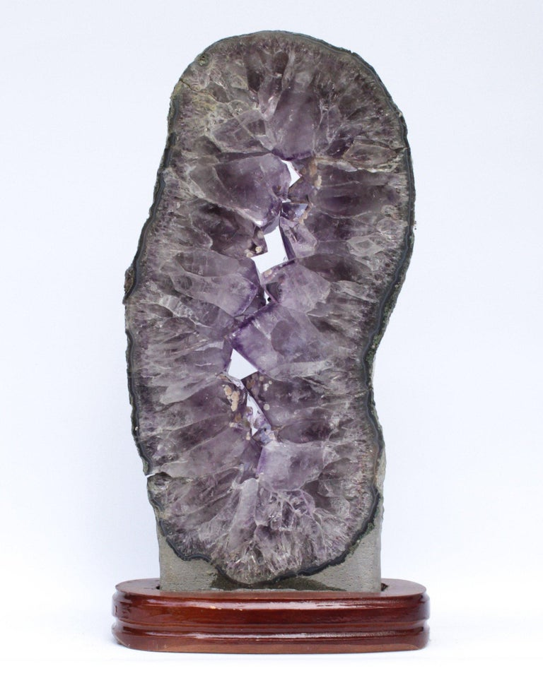Brazilian Amethyst Slice with Calcite Deposits and a Baroque Pearl on a Polished Wood Base For Sale