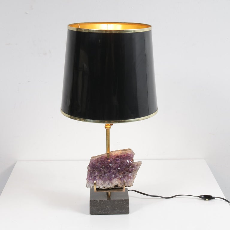 A rare table lamp with beautiful Amethyst core, in the style of Willy Daro, manufactured in Belgium around 1970.  The lamp has a beautiful brass base on a Belgian black marble foot. The hood is black lacquered with brass edges. The true eyecatcher