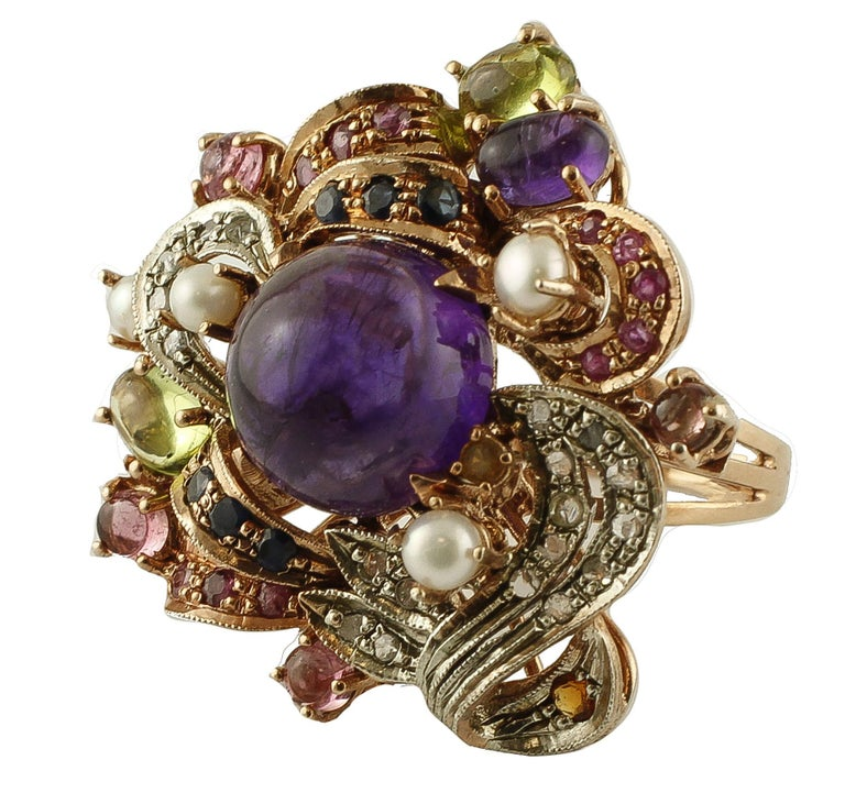 Beautiful retro ring in 9k rose gold and silver structure, mounted with a central intense amethyst, surrounded by flowery decorations in rose gold and silver studded with little diamonds, rubies, blue sapphires, peridots, garnets, amethysts and