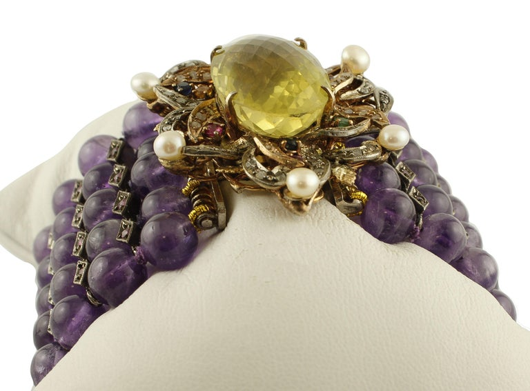 Astonishing beaded bracelet in 9k rose gold and silver structure, mounted with 5 rows of amethysts spheres adorned with rhomboidal silver details studded with rubies, and a very precious closure in rose gold and silver with central yellow topaz