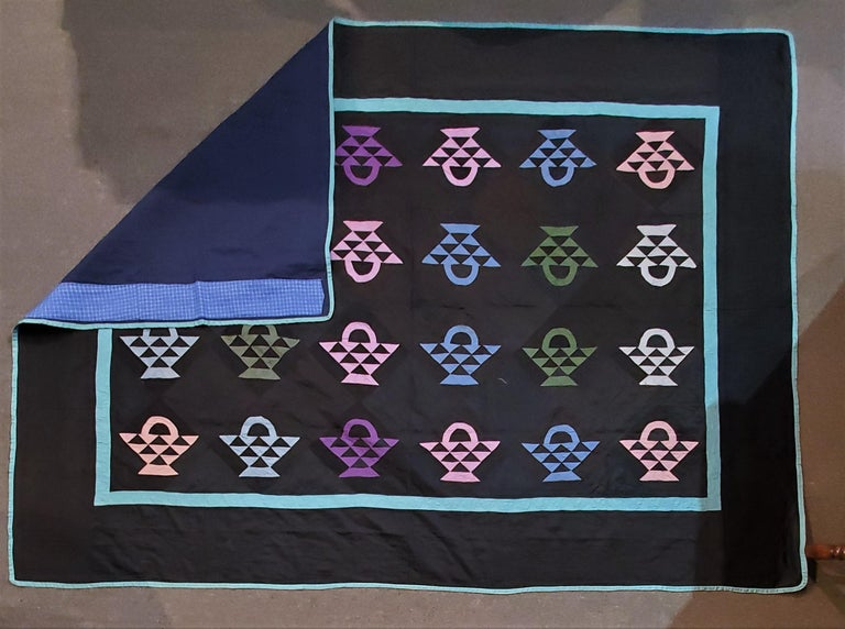 Beautiful authentic Amish quilt from Holmes Co., Ohio, circa 1930s The baskets are treadle machine, pieced in various shades of blue, green, pink and purple. Set with black cotton sateen. The inner border and binding are blue-green; it is quilted