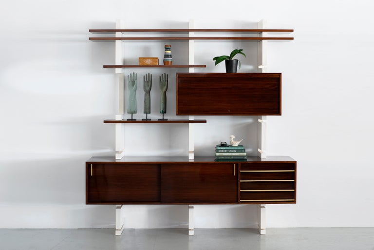 Modular bookcase beautifully refinished - Amma, Turin - Italy, 1960s  Floating rosewood cabinet with brass hardware - adjustable shelves and cabinet that opens to reveal drawers and more shelving.   Newly lacquered wood supports.   Gorgeous