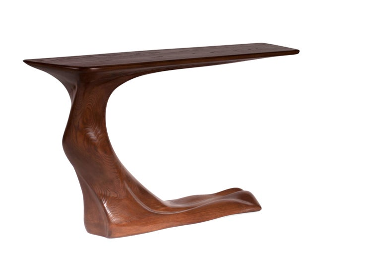 Frolic console table is a stylish futuristic sculptural art table with a dynamic form designed and manufactured by Amorph. Frolic console table is made out of solid ashwood natural stain with walnut stained finish. By the nature, the ashwood grain's