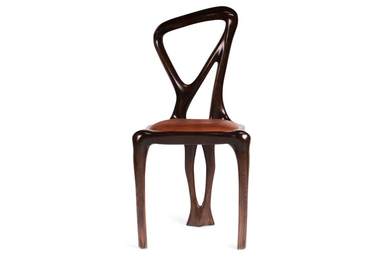 Dining chair designed by Amorph made out of solid ash wood and leather. It is stained dark walnut. Dimension: 38
