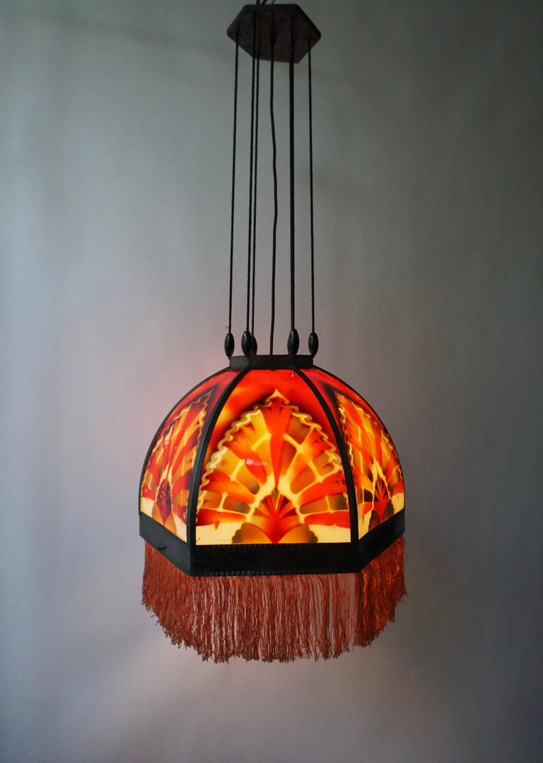 Beautiful 'Amsterdamse School' glass Art Deco pedant light, manufactured in the 1920s in the Netherlands. Very subtle Dutch design pendant in hexagon shape featuring 6 glass panels and beautiful colored glasses in a brass armature, with a