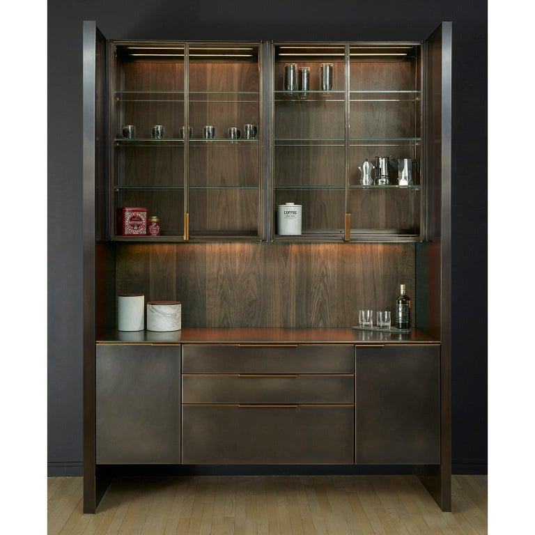 A bar system that blends individual functionality with Minimalist detailing. The interior cabinetry is fabricated from solid wood and handcut veneers offering the highest quality traditional woodworking techniques. The hand blackened stainless steel