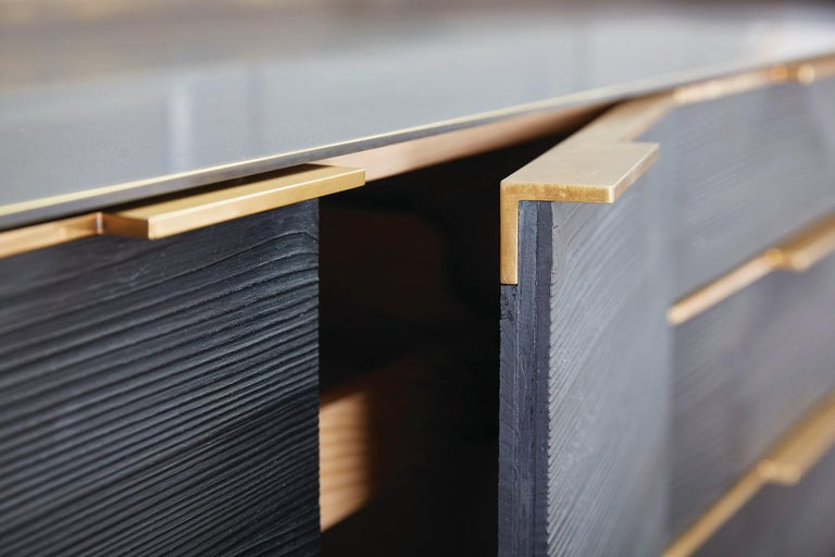 A darkened bronze surround with golden highlights creates the structure for a bold cabinet fabricated with charred pine door and drawer faces. The process to achieve the finish on the cabinet faces highlight the natural character of the wood in an
