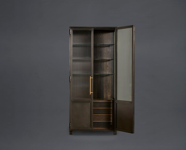 These versatile industrial-inspired cabinets bring strength and character to any space with their over-sized blackened steel and glass doors, framework and custom machined brass pulls. The interior of each cabinet offers truly flexible storage