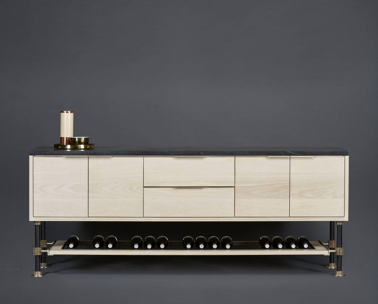 Amuneal's specialty Loft hardware in gunmetal and champagne brass is used to create this freestanding sideboard in bleached oak. The sideboard's lower shelf features a series of champagne brass rods in a blackened steel frame designed to provide