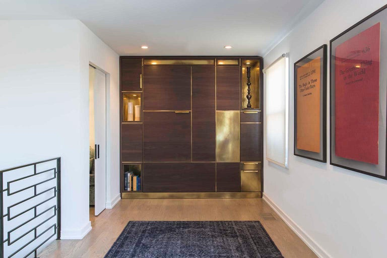 Designed to feel like a built-in piece of millwork Amuneal's Murphy bed conceals a queen-sized mattress behind panels of silvered walnut with warm brass inlays. With the bed closed, the walnut and brass panels work with brass clad cubbies and