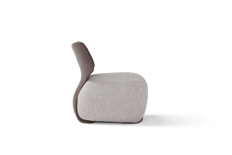 Noa armchair in grey upholstery and brown leather.
