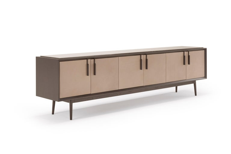 Theo is a modern take on a traditional furniture piece: the sideboard. The elegant wood container in dark oak is enriched by a refined detail: the leather upholstery of the doors, themselves enhanced by the slender oak handles. The base itself,