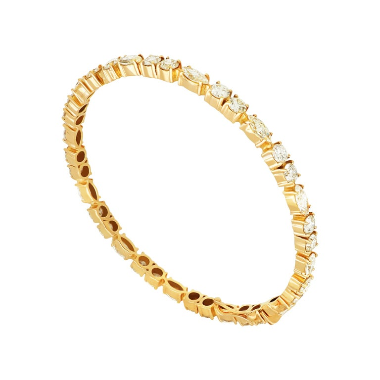 A contemporary line 18 karat yellow gold bangle featuring the round cut diamonds, punctuated by marquise diamonds to form a seamless stream of scintillation around the wrist.  Diamonds (Total Carat Weight: 7.48 ct)  18 Karat Yellow Gold Bangle Size: