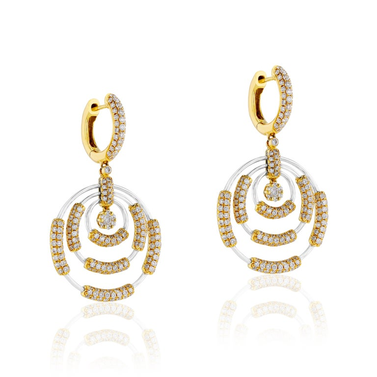 These timeless gold earrings from Amwaj Jewelry feature two round diamonds weighing 3.7 carats which form the centrepiece of the classically elegant 18 karat white gold earrings, framed by a radiant halo of yellow gold and small round white