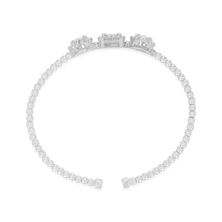 Showcasing the beauty of different diamond cuts, a graceful bracelet set with 3 remarkable portions of round and baguette cut diamonds that whirl endlessly around the wrist forming form the centre piece of this 18 karat white gold and diamond
