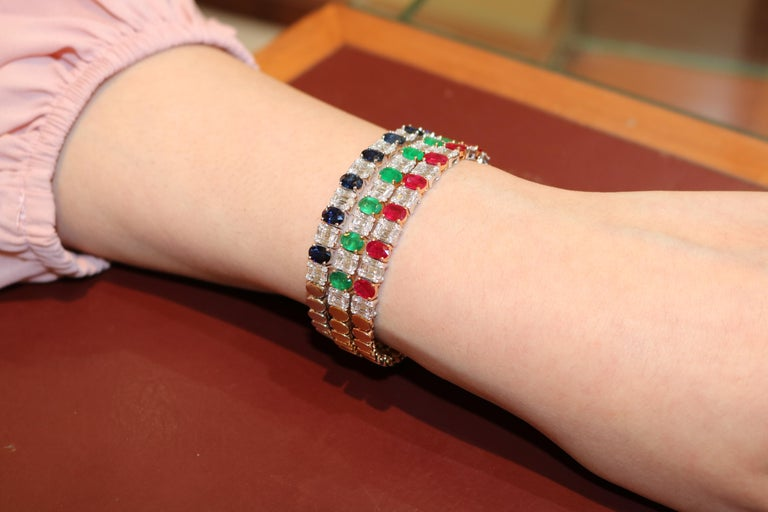 This 18 karat gold emerald cut bracelet features hypnotically radiant rubies, sapphires and emeralds set alongside sparkling white diamonds revealing our masterful craftsmanship of the finest emerald cut jewels. The classic gemstone and diamond