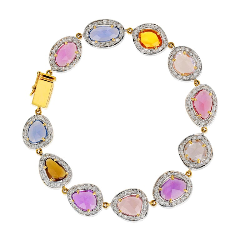 A timeless bracelet comprising multi-color sapphires, matched with small round cut white diamonds weighing 2.21 carats. The design of this white gold bracelet makes it a classic bracelet to treasure. Each sapphire is selected for its rich hue,