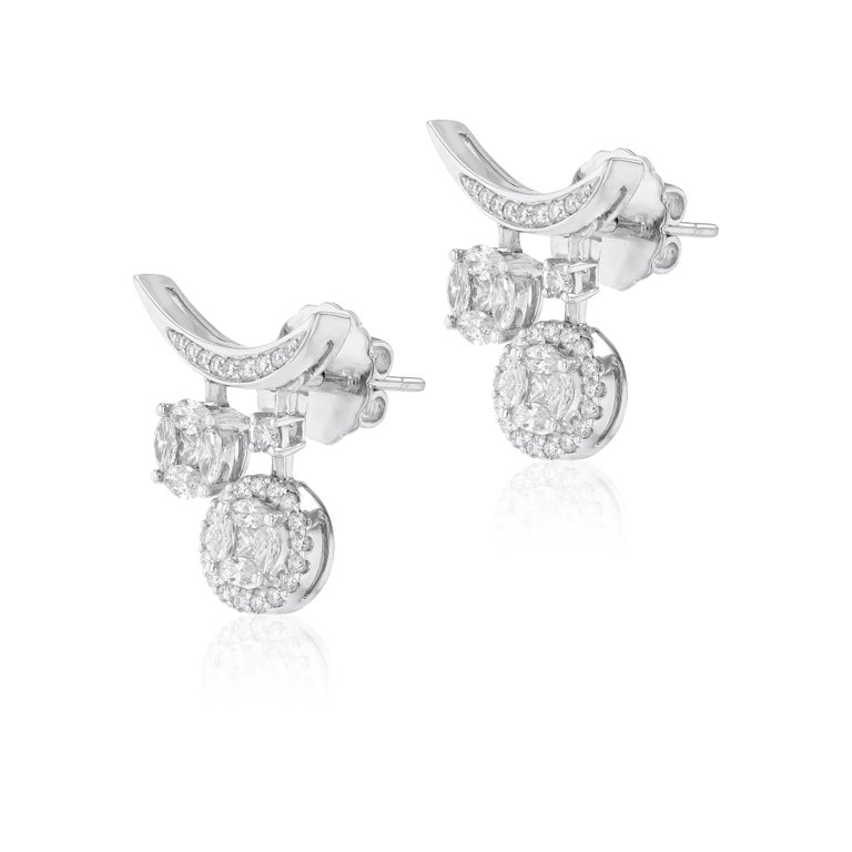 A petite yet powerful incarnation of crescent, the 18 karat white gold earring is illuminated by round cut diamonds that is given vibrant accents by their delicate wings. Suspended from each side 2 exquisite small to medium round shape diamonds that