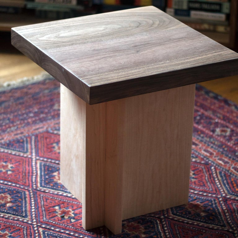 This is a solid walnut and maple side table or small stool. The profile is asymmetrical and architectural while celebrating the natural wood elements.   Customizable.